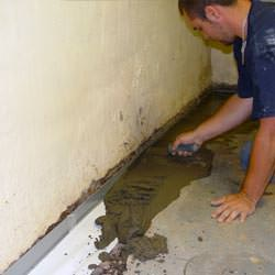 A basement waterproofer installing a perimeter drain system in Pearl River